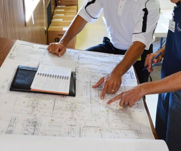 Two project team members reviewing floor plans