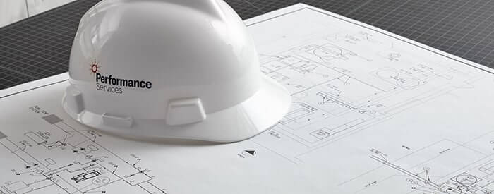 Performance Services branded hardhat sitting on top of a set of building plans