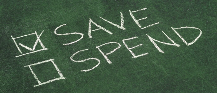 Chalkboard writing of savings vs. spending