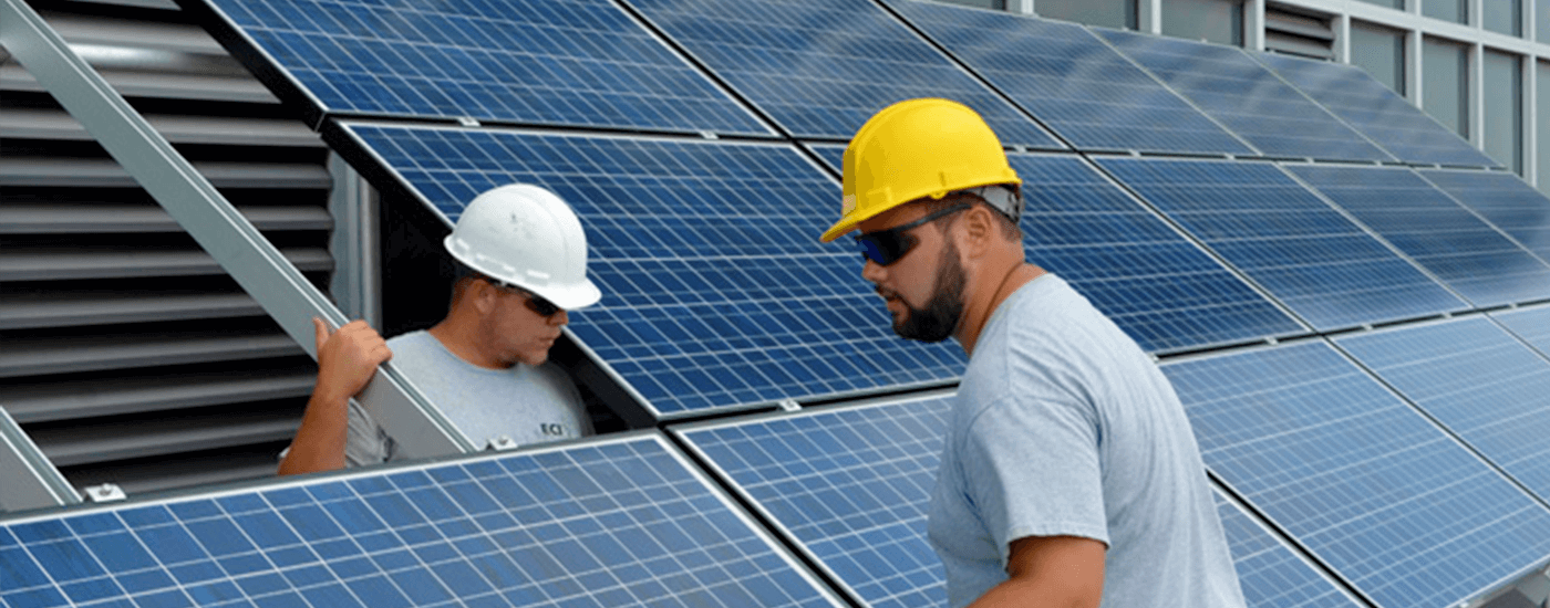 Two construction workers installing solar panels